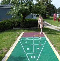 Naturist woman playing shuffleboard